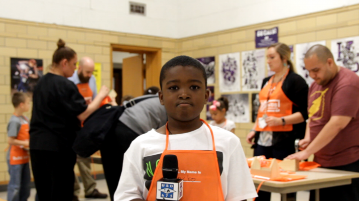 Student in Home Depot Apron holding Microphone