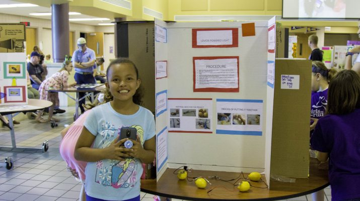 Girl Standing next to Science Experiement